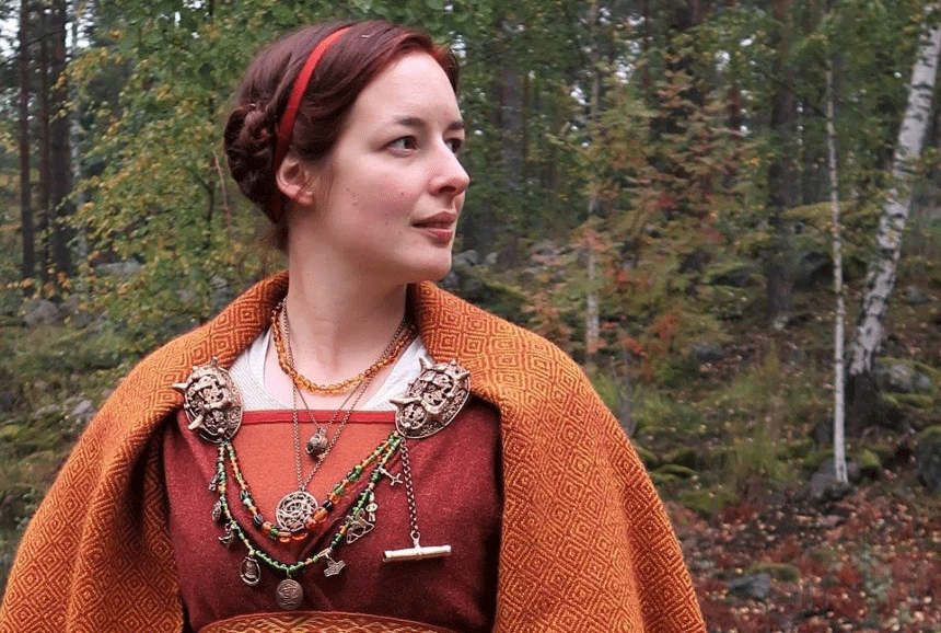Young viking woman in forest setting.